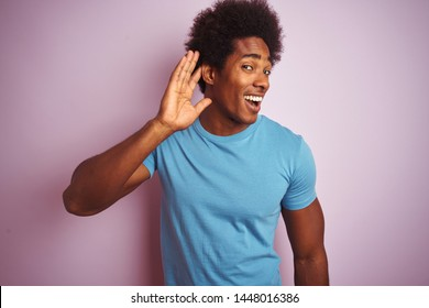 African american man with afro hair wearing blue t-shirt standing over isolated pink background smiling with hand over ear listening an hearing to rumor or gossip. Deafness concept.