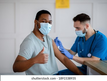 African American man in antiviral mask gesturing thumb up during coronavirus vaccination, approving of covid-19 immunization. Young doctor giving vaccine injection to male patient