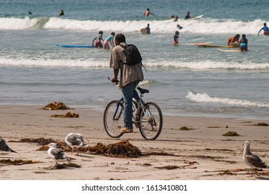 African american man with backpack on bicycle riding on beach with people playing in the water in the background