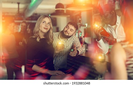 African american man bartender making alcohol cocktail for couple in nightclub