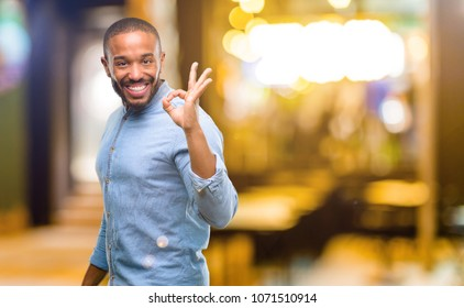 African american man with beard doing ok sign with hand, approve gesture at night