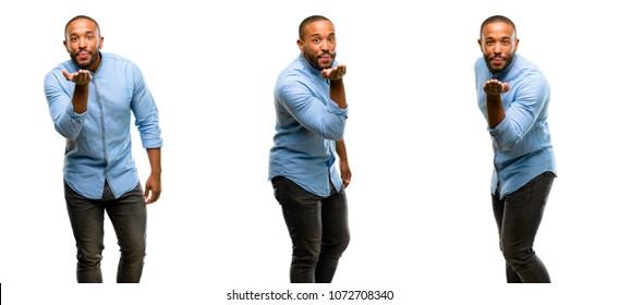 African american man with beard expressing love, blows kiss at camera, flirting