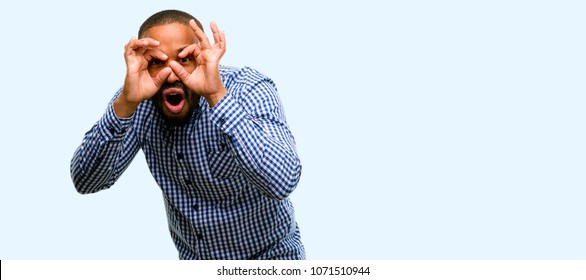 African american man with beard looking at camera through fingers in ok gesture. Imitating binoculars isolated over blue background