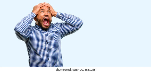 African american man with beard stressful keeping hands on head, terrified in panic, shouting isolated over blue background
