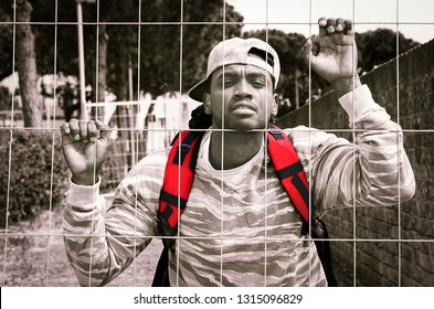 African american man bihind wire mesh in sad facial expression - Young refugee male holding metal fence - Concept of barriers to freedom with dramatic black and white filter and highlighted red colors