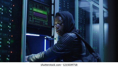 African American man in black outfit hacking servers of data center launching DDoS attack