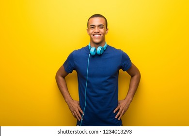 African american man with blue t-shirt on yellow background posing with arms at hip and laughing looking to the front
