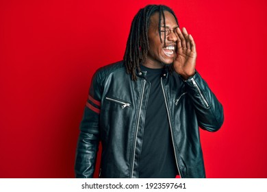 African american man with braids wearing black leather jacket shouting and screaming loud to side with hand on mouth. communication concept.