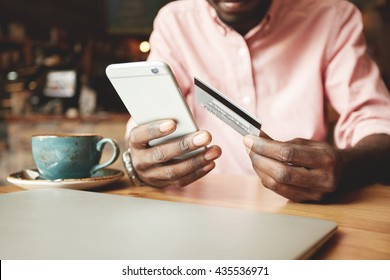 African American man in casual shirt paying with credit card online while making orders via the Internet. Successful black businessman making transaction using mobile bank application. Selective focus