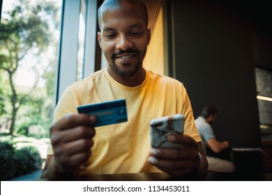 African American man in casual yellow tshirt paying with credit card online while making orders via mobile Internet. Attractive black hipster male making transaction using mobile bank application.