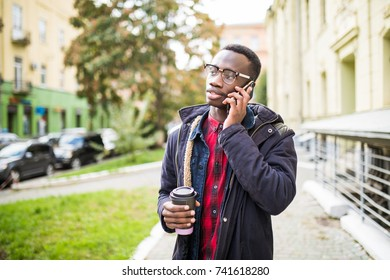 African american man checking his phone and holding a coffee