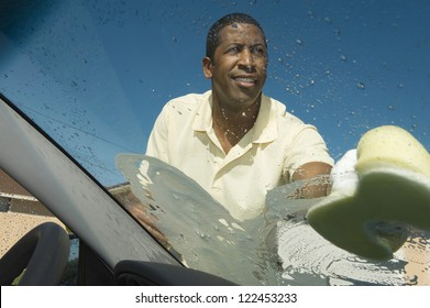 African American man cleaning windshield of car