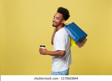 African American man with colorful paper bags isolated on yellow background