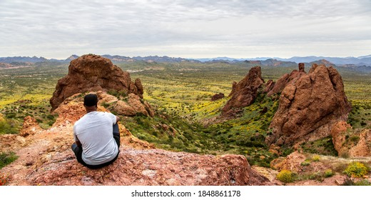 African American man contemplating the view from The Flatiron in the Superstition Mountains from Treasure Loop Trail. Hiking in the Arizona desert panoramic. Moutain peak hike banner.