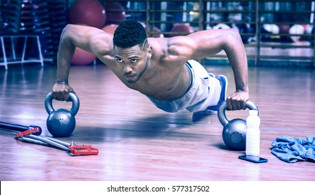 African american man doing push up workout in dark gym using kettlebell - Black gritty face guy working on chest muscles exercise at fitness center - Bluish vintage filter look with dim light effect
