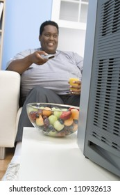 African American man drinking juice while watching television with a bowl of fruit in the front