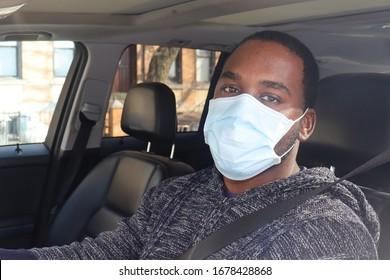 African American Man Driving car wearing medical mask