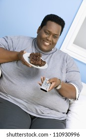 African American man eating donut while watching television