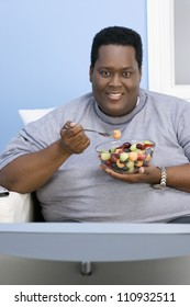 African American man eating fruits while watching television