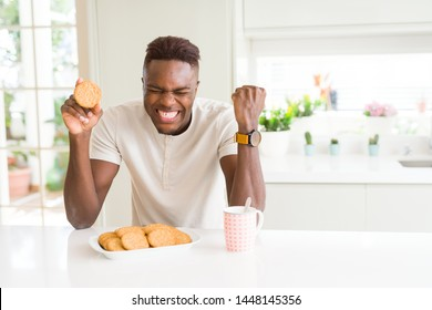 African american man eating healthy whole grain biscuit screaming proud and celebrating victory and success very excited, cheering emotion