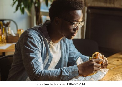 african american man enjoying the taste of hamburger.handsome and young afro man in a stylish shirt and glasses holding a burger on a white background.love of junk food diet
