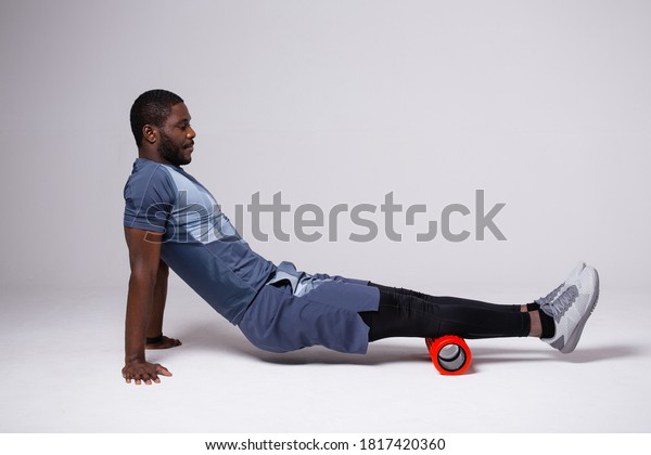 African American man exercising with massage roll on white background. Works on the fascia of the back of the thigh.