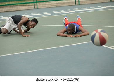 African american man friends playing on street basketball court. Real authentic activity.