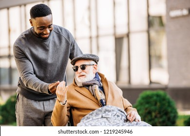 african american man giving joint to senior disabled man in wheelchair wjhile they spending time together on street