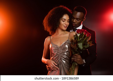 african american man giving red roses to curly girlfriend in dress on black