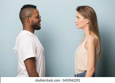 African American man in glasses and beautiful Caucasian woman looking at each other eyes to eyes, sideways view, diverse couple in love, support and care, isolated on studio background