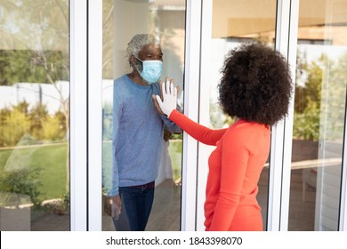 African American man greeting his adult daughter through window door, wearing face mask. Social distancing and self isolating at home during Coronavirus Covid 19 quarantine lockdown.