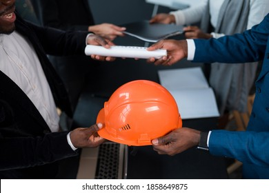 An African American man hands over a building permit and an orange construction helmet to an investor. The concept of business, construction, financing
