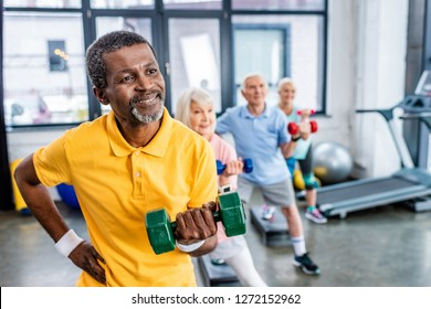 african american man and his friends synchronous exercising with dumbbells at sports hall