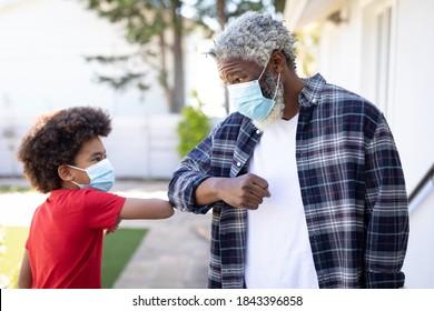 Afroamerikaner und sein Enkel, mit Gesichtsmasken, berührenden Ellenbogen, Gruß. Soziale Distanzierung und Selbstisolierung zu Hause während Coronavirus Covid 19 Quarantäne Sperrung.