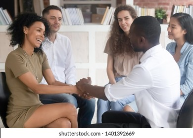 African American man hold hands of relieved biracial woman show support and understanding at group therapy session, diverse people psychotherapy training sit in circle undergo psychological treatment