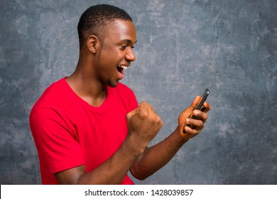 African American man holding his mobile phone celebrating his victory, success  on winning a lottery ticket. man viewing something interesting on his phone