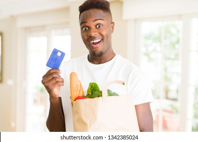 African american man holding paper bag full of groceries and holding credit card as payment