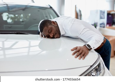 african american man hugs new car he dreams about, he stand in cars showroom next to white automobile, want to buy it
