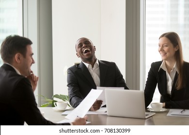 African american man laughing during successful negotiations with caucasian partners. Job applicant made pleasant first impression on recruiters with joke at interview. Good relationship in office