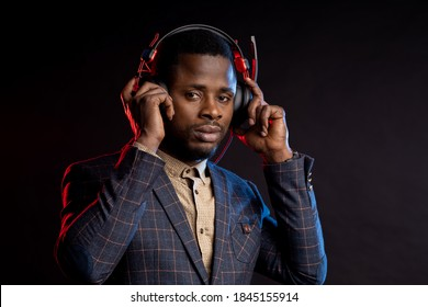 african american man listening music in headphones in dark. Portrait of stylish DJ with headset, wearing checked suit, isolated on black background