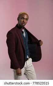 african american man looking at camera while holding side of his jacket on pink background