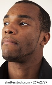 An african american man looking into the distance. Closeup headshot.