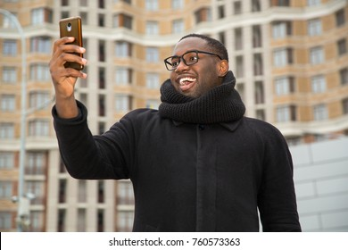 African american man making himself selfie portrait of smart phone. Talk through video communication, video call. Shoot with the phone.