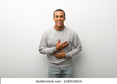 African american man on white wall background smiling a lot while putting hands on chest