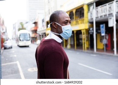 African American man out and about in the city streets during the day, wearing a face mask against air pollution and covid19 coronavirus, crossing the street.