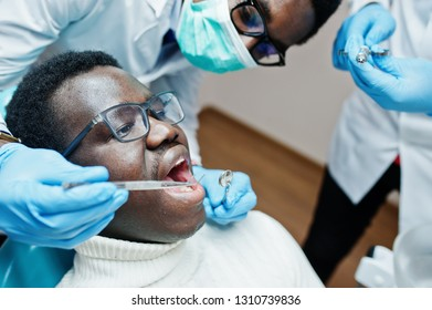 African american man patient in dental chair. Dentist office and doctor practice concept. Professional dentist helping his patient at dentistry medical. Injection anesthetic.