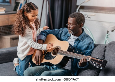 African american man playing guitar with his cute daughter