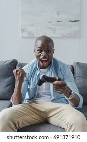 African american man playing video game with joystick at home