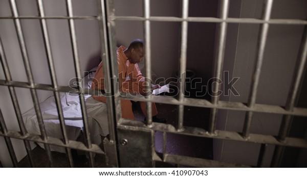 Hombre afroamericano en prisión - leyendo la Biblia tras las rejas