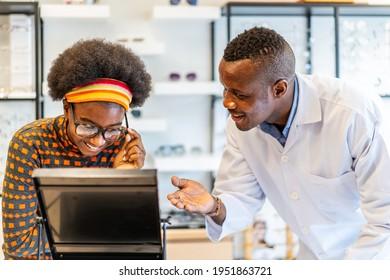 Afroamerikaner-Optiker-Helfer und verkaufen junge afrikanische Amerikanerin Brille in Optikerladen. die korrekte oder fehlerhafte Sehkraft verwendet.